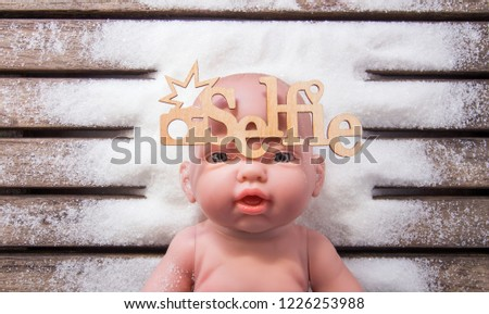 Baby doll selfie at Christmas. Snow background. Conceptual photo