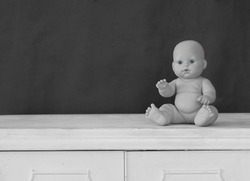 Baby doll sitting on vintage table