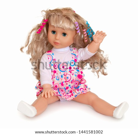 Baby doll with blonde hair wearing colourful dress and white polo neck isolated on the white background. Front view of a sitting plastic female wearing clothes with pink and blue circular patterns.