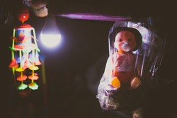 baby dolls lit by a bulb in a local outdoor market in a south indian village