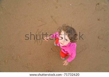 baby draws on sand beach