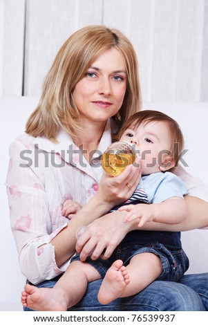 Baby drinking juice on mum's knees