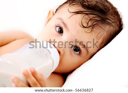 Baby drinking milk and looking at the camera. White Background