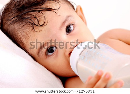 Baby drinking milk of her bottle. White background - stock photo