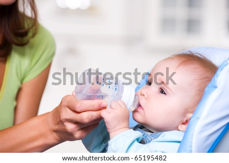 Baby drinking water from bottle sitting  in the highchair in kitchen