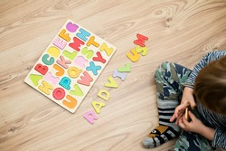 Baby early learning. Wooden letters of the alphabet. Children reading puzzle. Kids educational game, match the right place. Teaching develop intellectual kid game board.