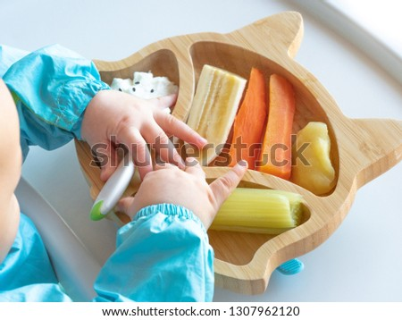 Baby eating by hands, Baby eating organic bio vegetables with BLW method, baby led weaning. Happy vegetarian kid eating lunch. Toddler eat himself, self-feeding. infant baby eating.