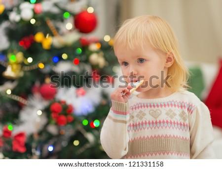 Baby eating Christmas cookies near Christmas tree