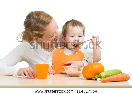baby eating vegetables puree by spoon and sitting on mother laps