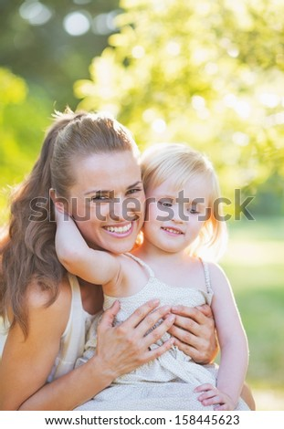 Baby embracing mother outdoors