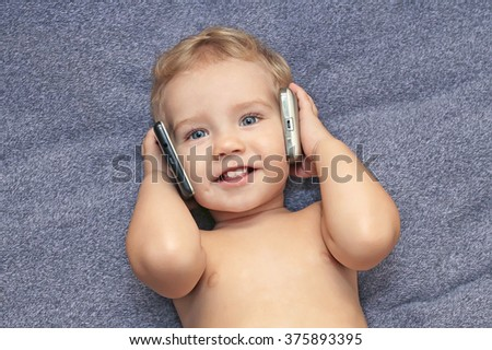 Baby European appearance talking on two phones at once. A child with a black and white telephone smartphone Сток-фото ©