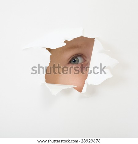 Baby eye peep through hole in sheet of paper. Concept of childish curiosity