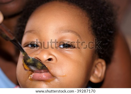 baby feeding with food filled face