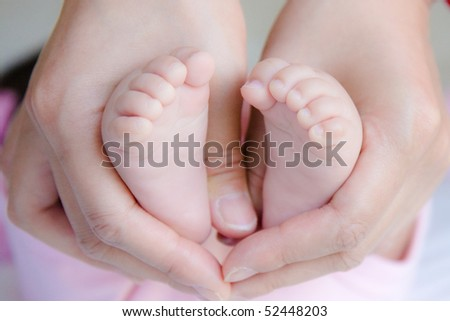 baby feet are held in mommy's hands tightly