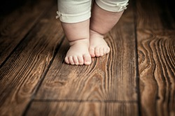 Baby feet doing the first steps. Baby's first steps. Baby feet .