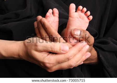 Baby feet held by mother and father's hands.