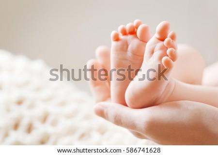 baby feet in mother hands. mom...