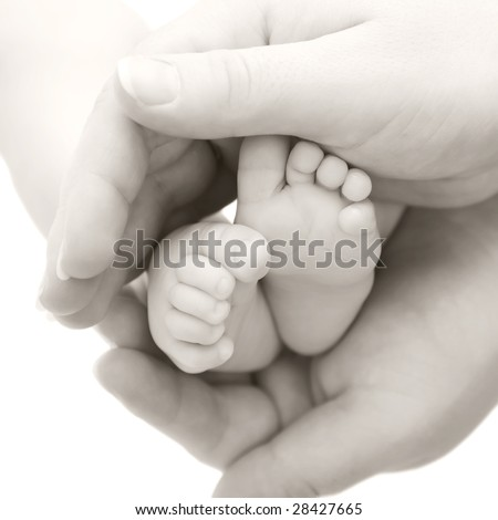 Baby feet in mother's hands, black and white image.