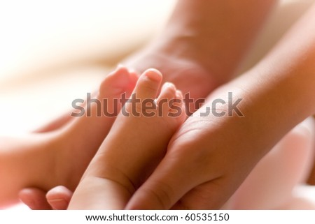 Baby feet in mothers hands (soft focus, shallow depth of field)