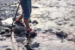 Baby feet in the stream. Game, building a dam. Happy childhood in nature. Crossing a mountain river to a ford. Little hiker tourist. Hiking with children. Legs Lifestyle