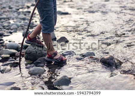 Baby feet in the stream. Game, building a dam. Happy childhood in nature. Crossing a mountain river to a ford. Little hiker tourist. Hiking with children. Legs Lifestyle Foto stock ©
