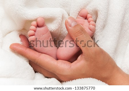 Baby feet with Mom's hand on white coverlet.