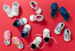 Baby first steps. Kids shoes variety on red color background, top view. Children footwear, girl and boy booties and soft infant shoes flat lay