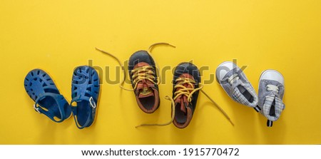 Baby first steps. Three pairs of boy blue shoes variety on yellow color background, top view. Kids footwear, beach sandals, booties and soft infant shoes in a row. Foto stock ©