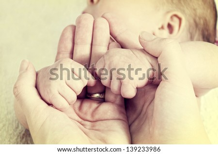 Baby fists in the mother hands