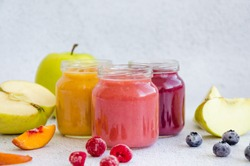 Baby food. Homemade fruit puree. Variety of apple puree or applesauce with frozen peach, raspberries and blueberries in three glass jars on a light background. Healthy food. Horizontal, copy space