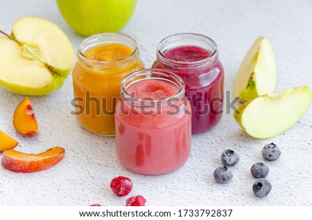 Baby food. Homemade fruit puree. Variety of apple puree or applesauce with frozen peach, raspberries and blueberries in three glass jars on a light background. Healthy food. Horizontal.
