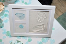 Baby footprint and handprint on clay mold plaque in a frame. To remember in the future how small the baby was. Cute frame images cheerful childhood celebration event. Baby DIY keepsake to keep forever