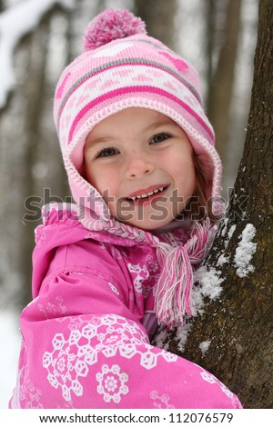 Baby girl and the first snow in the forest