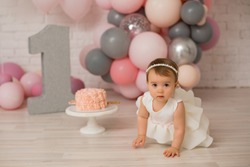 Baby girl  at first birthday with smash cake