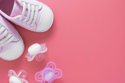 Baby girl background. Newborn shoes with pacifiers, pink background with copy space.