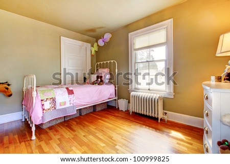 Baby girl bedroom interior with pink bed and hardwood floor.
