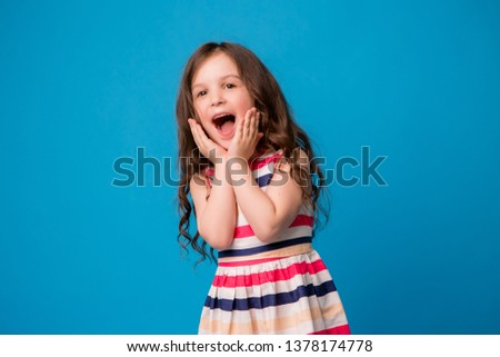 baby girl brunette in colorful dress smiling, isolate on blue background, children's emotions,Close-up portrait of dark-haired little girl  smiling on isolated background  #1378174778