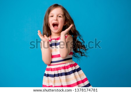 baby girl brunette in colorful dress smiling, isolate on blue background, children's emotions,Close-up portrait of dark-haired little girl  smiling on isolated background  #1378174781