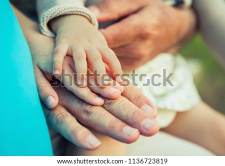 Baby girl, child and senior man comparing the hands size. Two different generations concept.
