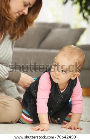 Baby girl crawling on floor with mum sitting in the background.?