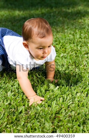 baby girl crawling on green grass