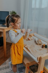 Baby girl decorating easter eggs on white table. Happy child painting eggs with dots. Dotty Easter eggs on kraft paper background.