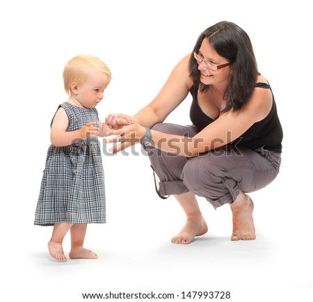 Baby girl doing her first steps with mother help. Studio shot on white background.