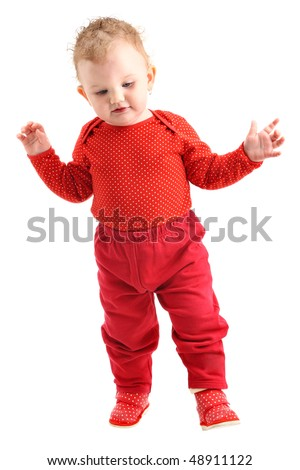 Baby girl dressed in red learning to walk isolated on white