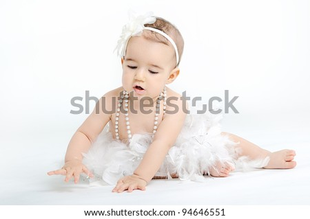 Baby girl dressed in white tutu and wearing big flower headband