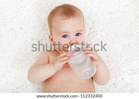 Baby girl drinking water from feeding bottle - laying on white rug