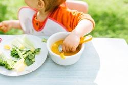 Baby girl eating her lunch in the garden outside in summer
