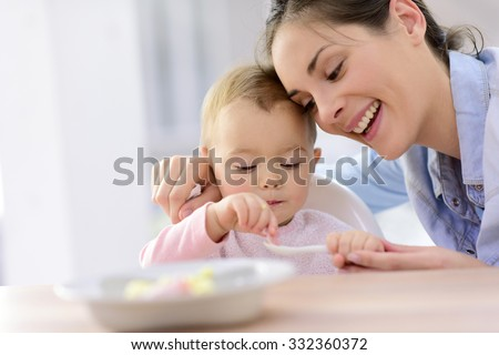 Shutterstock Baby girl eating lunch with help of her mommy
