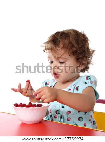 Baby girl eating raspberry
