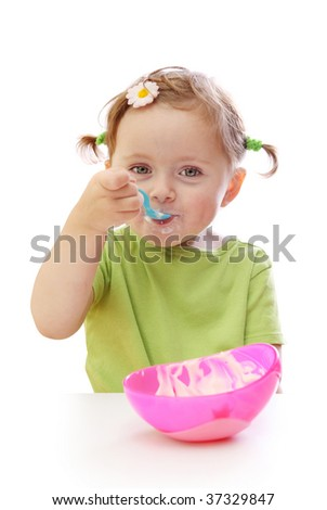 Baby girl eating yoghurt isolated on white background